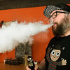 Shane Mullins, of SWMO Vapes takes a draw off an atomizer on Wednesday. Atomizers line a shelf at SWMO Vapes on Wednesday. Local governments are considering raising the legal age to buy tobacco and vaping supplies to 21.<br /> Globe | Laurie Sisk