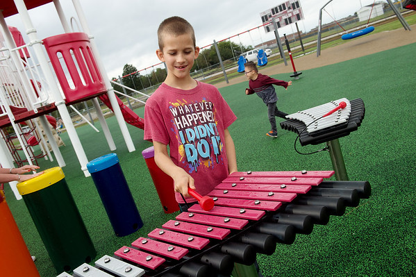 Dakota Meyers, third grade, plays music at the Power of Play playground in Carl Junction on Thursday.<br /> Globe | Roger Nomer