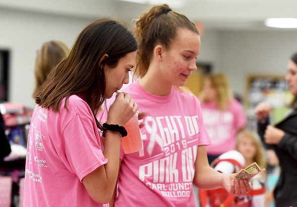 From the left: Carl Junction volleyball players Tatum White and Jocelyn Brown enjoy a Pink Drink during the The 2019 Pink Out on Tuesday night at CJHS. The event, in its 12th year, raised $3,975 to benefit the Hope 4 You Breast Cancer Foundation.<br /> Globe | Laurie Sisk