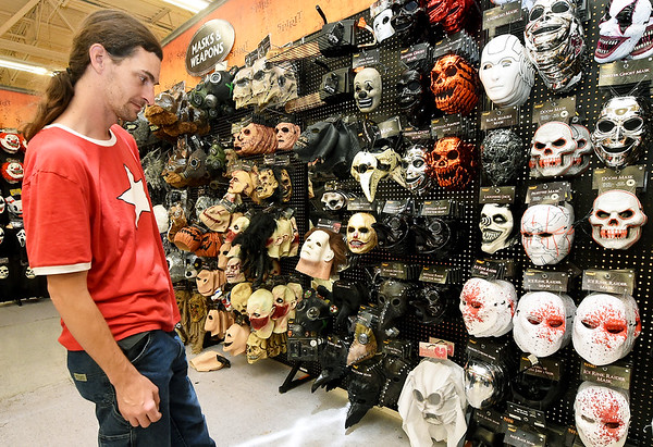 Thomas Hasler checks out the selection of scary masks while shopping Wednesday at Spirit Halloween.<br /> Globe   Laurie Sisk
