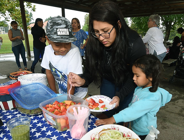 From the left: Viktor Alvarado, 6 Ale Martinez and Mia Alvarado, 4, sample the fare during a reunion picnic for the Carthage Public Library Citizenship Class on Saturday at Municipal Park.<br /> Globe | Laurie Sisk