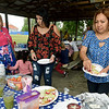 From the left: Berta Mojica, Alicia Mojica and Roxana Lopez partake in picnic fare during the Carthage Public Library Citizenship Class's reunion on Saturday at Municipal Park. Alicia Mojica and Lopez are graduates of the class.<br /> Globe | Laurie Sisk