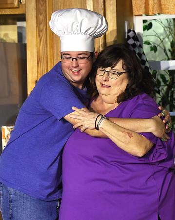 From the left: Dewey Frye Jr., (portrayed by Abram Stiegman) hugs his mom, Dorothy Frye (Kelly Weaver) during dress rehearsal for the Stained Glass Theatre Joplin production of Southern Fried Funeral on Tuesday night at SGTJ.<br /> Globe   Laurie Sisk
