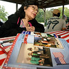 With a photo book of memories in the foreground, Abigail Rodriguez talks about her experience in the Carthage Public Library Citizenship Class during a reunion on Saturday at Municipal Park. Rodriguez, who was already a citizen, said she took the class to help improve her English language skills.<br /> Globe | Laurie Sisk