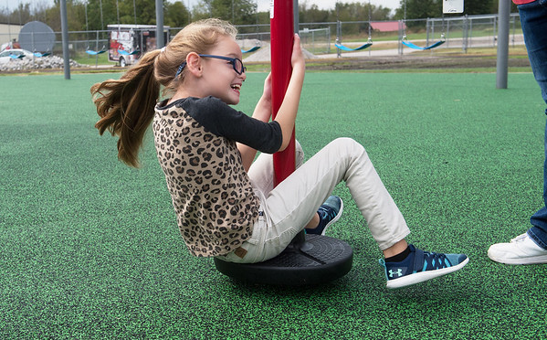 Abigail Flinn, third grader, spins on a the Power of Play playground in Carl Junction on Thursday.<br /> Globe | Roger Nomer