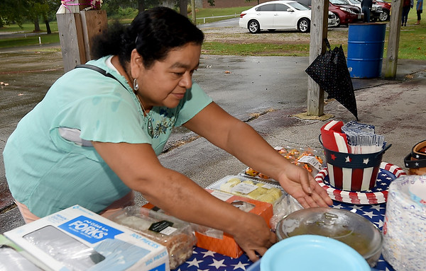 Erika Gutierrez contributes a beef casserole to the fare during a reunion picnic for graduates, staff and friends of the Carthage Public Library Citizenship Class on Saturday at Municipal Park.<br /> Globe | Laurie Sisk