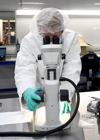 Engineer Tim Breuer looks into a microscope while working in the medical power division of Eagle Picher Technologies on Thursday.<br /> Globe | Laurie Sisk