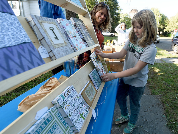 Eight-year-old Maggie Neuenschwander checks out the selection of handmade journals as Cody Martin looks on at a stand operated by Martin and her husband, John Martin during Porchfest on Saturday. The grassroots music festival took place on various porches in the North Heights neighborhood of Joplin and also featured 24 bands and a food truck alley.<br /> Globe | Laurie Sisk