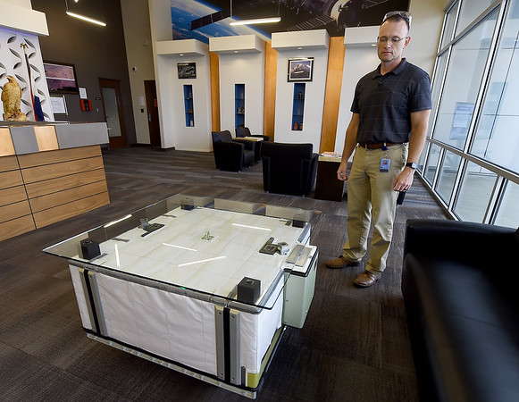 Eagle Picher Technologies Director of Operations Travis Brown stands near a battery-turned-coffee table that was used in the international space station and is now on display in the lobby of Eagle Picher.<br /> Globe | Laurie Sisk
