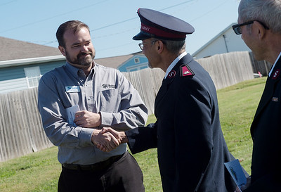 Scott Clayton, executive director of Joplin Area Habitat for Humanity, left, shakes hands with Salvation Army Major Phil Aho during the groundbreaking for the 22nd new house in the partnership between the two organizations on Monday.