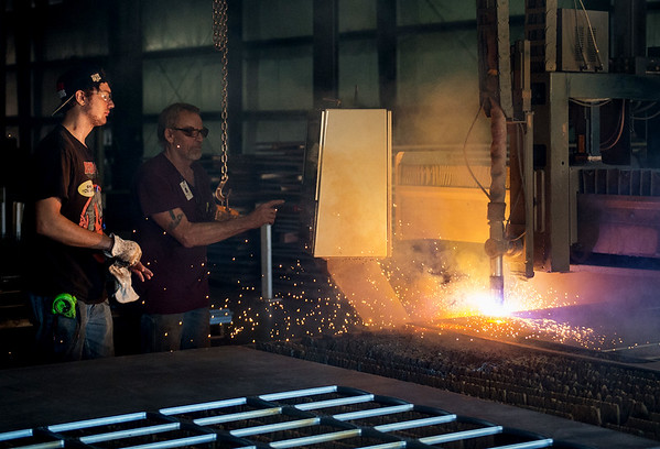 Justin Petty, welder, left, and Jerry Harmon, plasma operator, use a plasma cutter at Cardinal Scale on Wednesday.<br /> Globe | Roger Nomer