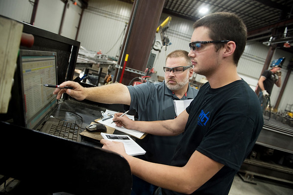 Travis Keeton, scale shop supervisor, left, works with Zachary Stephens, saw operator, to program a robotic welder on Wednesday at Cardinal Scale.<br /> Globe | Roger Nomer