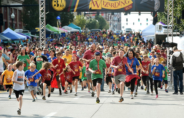 Some of the nearly 1,500 participants race off the starting line during the Wizarding Run and Downtown Joplin Fall Festival on Saturday in downtown Joplin.<br /> Globe | Laurie Sisk