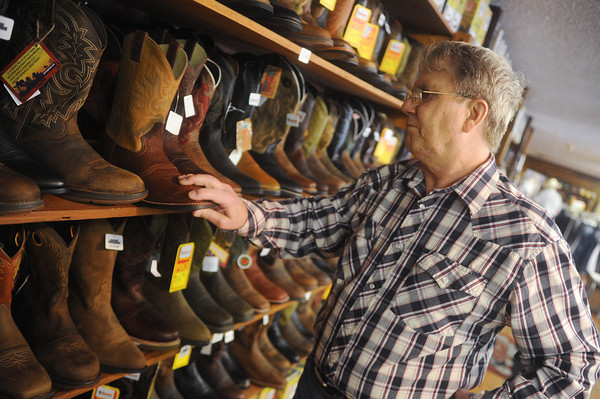 Globe/Roger Nomer<br /> Steve Anderson, owner of Anderson's Western Wear along Range Line Road, arranges boots at his store on Tuesday.