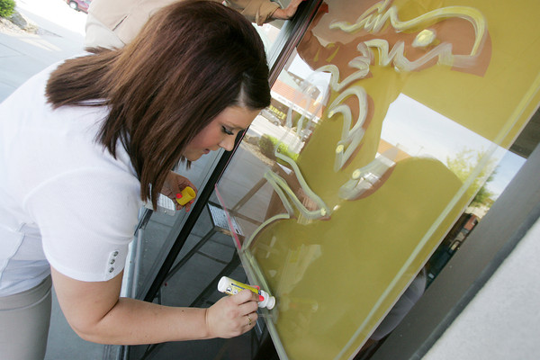 Globe/Roger Nomer<br /> Korie Bitner, service representative at BMO Harris Bank, paints the Pittsburg State mascot on the bank's downtown location on Wednesday afternoon.  Pittsburg businesses participated in the Paint the Town Red campaign before PSU's first football game.