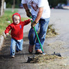 Three-year-old Jacob Rhodes of Joplin helps his grandfather William Rhodes of Wentworth push a broom to clean yard waste off the street during the Great Day of Service, Sunday morning, Sept. 29, 2013, in the 100 block of North Joplin Street.<br /> Globe | T. Rob Brown