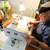 "Terry Barton of Pittsburg, Kan., researches uniform colors and styles in the book ""Regiments & Uniforms of the Civil War"" Thursday afternoon, Sept. 26, 2013, in his home. Barton said he researches for his miniatures work to make it as historically accurate as possible with period uniforms and detailed bases. Some of his bases even incorporate actual grass from historic Civil War battlefields.<br /> Globe 
