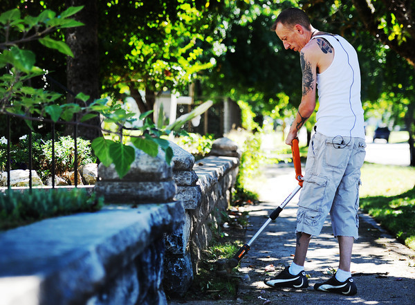 "Chris Warren uses a battery-powered weedeater to trim his yard Monday afternoon, Sept. 23, 2013, in the 700 block of South Moffet. ""I like this,"" Warren said. ""I'm a barber by trade. This is like giving a haircut only on a larger scale.""<br /> Globe 