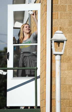 Niamh Quinn, an MSSU international student from the University of Ulster--Coleraine in Ireland, helps clean a resident's window during the Great Day of Service, Sunday morning, Sept. 29, 2013, in the 400 block of North Joplin Street.<br /> Globe | T. Rob Brown