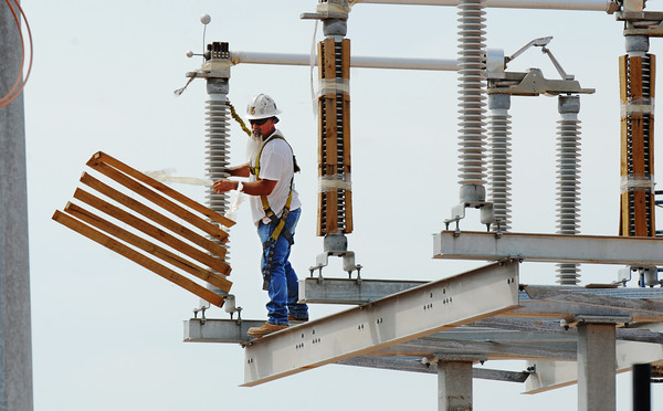 A construction worker removes protective packaging Thursday morning, Sept. 12, 2013, while installing large electrical infrastructure on part of the new Empire District Electric Company site at the Crossroads Industrial Park.<br /> Globe | T. Rob Brown