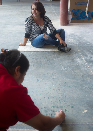 Globe/Roger Nomer<br /> Nazlije Jennings takes a look around the new Irving Elementary as Carmen Martinez writes a message to its students on Monday.  Both women have boys that are students at the school.