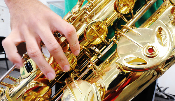 The hand of Quapaw (Okla.) High School senior Jesse Morton practices the barisax in the music room Friday afternoon, Sept. 13, 2013, at the school.<br /> Globe | T. Rob Brown