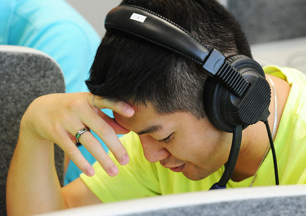 Andy Tran, an MSSU junior psychology major, reads Spanish to a classmate through a headset Friday morning, Sept. 27, 2013, in the Foreign Language Lab in MSSU's Webster Hall.<br /> Globe | T. Rob Brown