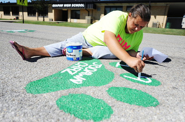 """Lacey Richardson of Quapaw, secretary-treasurer of the Quapaw Community Booster Club, paints a paw print and donor's graduation year Friday afternoon, Sept. 13, 2013, in front of Quapaw High School. Funds raised from the sale of more than 100 paw prints go toward the Hay Days Festival, other activities and to create new scholarships next spring. """"We will sell them until it's too cold to paint,"""" Richardson said.<br /> Globe 