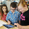 Globe | T. Rob Brown<br /> Aidan Leas (center), 13, of Joplin looks over an iPad Mini display with his best friend Dany Koff (right), 13, of Joplin, and his sister, Parker Leas, 10, just before buying one Wednesday evening, Sept. 25, 2013, at Joplin's Best Buy. Leas has a learning disability and relied on his iPad for communication -- it came up missing on his birthday, believed to have been stolen. Some good Samaritans who found out via Facebook about the situation and pulled together money to help the boy replace it.