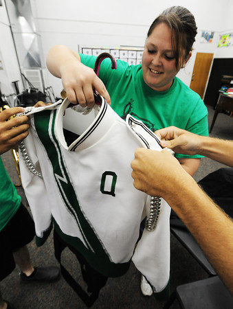 Quapaw (Okla.) High School Band Director Sarah Fanning straightens out a uniform with help from the hands of Jesse Morton (right) and Jakob Way in the music room Friday afternoon, Sept. 13, 2013, at the school.<br /> Globe | T. Rob Brown