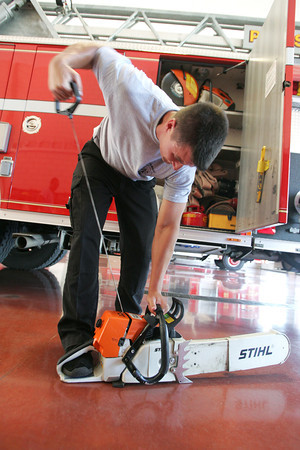 Globe/Roger Nomer<br /> Firefighter Tyler Johnson tests the department's chainsaw at the Pittsburg Fire Department on Wednesday.