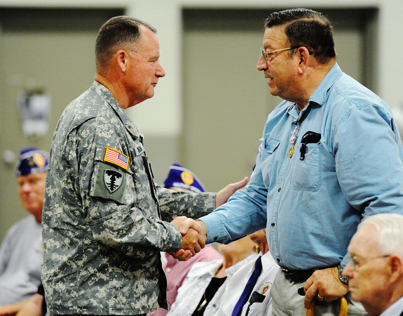 Brig. Gen. J. Marty Robinson (left), assistant adjutant general--Army (support), Missouri Army National Guard, shakes hands with Ret. Maj. Paul Harvey Jr., who served in the U.S. Army during the Vietnam War, after presenting him with a medal during the Patriot's Day Veterans Award Ceremony Wednesday afternoon, Sept. 11, 2013, at the Missouri National Guard Armory on 32nd Street in Joplin. The event was sponsored by the MOAA Four State Chapter in cooperation with the Guard, the Missouri Veterans Association and the state of Missouri.<br /> Globe | T. Rob Brown