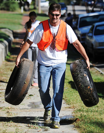 Dwayne Friend of Joplin lugs two old tires out of a resident's yard during the Great Day of Service, Sunday morning, Sept. 29, 2013, in the 200 block of North Joplin Street.<br /> Globe | T. Rob Brown