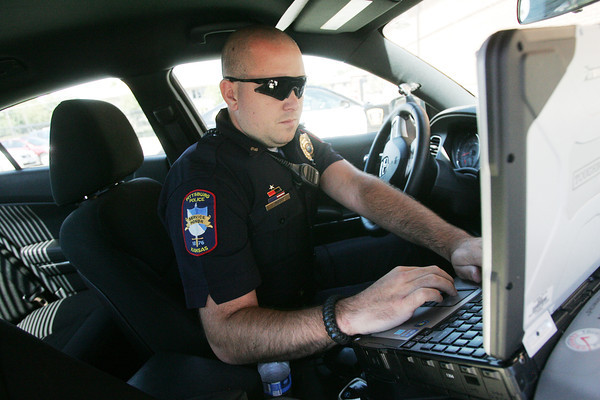 Globe/Roger Nomer<br /> Acting Sergeant Chris Moore works on a computer at the Pittsburg Police Station on Wednesday.