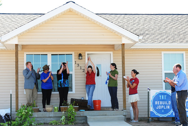 New home owner Emily Morrison (center) reacts after cutting the ribbon as others clap during the Rebuild Joplin Open House for her home Thursday morning, Sept. 26, 2013.<br /> Globe | T. Rob Brown