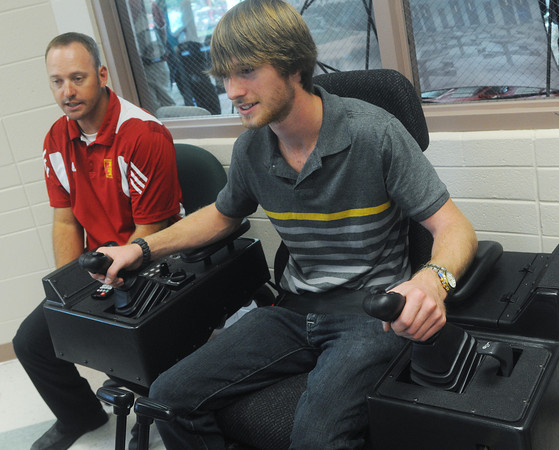 Globe/Roger Nomer<br /> Chad Crain, research technologist with the Pittsburg State Construction Program, guides James Bradford, a freshman at John Brown University, through the CAT simulator during Company Day on Wednesday.