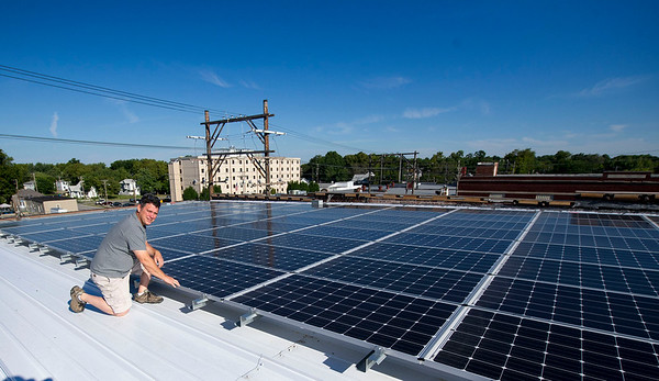 Contractor Jeff Neal, of Neal Group Construction, kneels near the 44.5kw solar system he installed on the roof of the Hurlbut Building he is renovating for office space on at 212 S. Joplin. The project is one of many Neal has taken on in downtown Joplin.<br /> Globe | Laurie Sisk