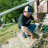Jonathan Fleischmann, of Impact Life Church, clears steps of weeds on North Byers during the Great Day of Service on Sunday. Fleischmann was one of about 30 members of the church who donated their services to the effort.<br /> Globe | Laurie Sisk