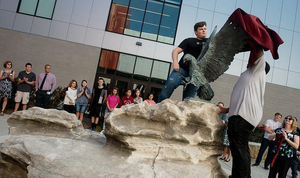 Globe/Roger Nomer<br /> Nicolai Birch, left, Joplin High senior, and Demetrius Williams, junior, help unveil the bronze eagle on Wednesday in the Joplin High Rose Garden.