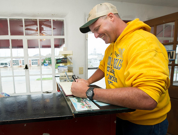 "Traveler Troy Jordan, of St. Joseph, signs the guestbook at Boot's Court Motel on Friday. Jordan, a return visitor, was traveling with a motorcycle group known as the ""Geezers.""<br /> Globe 
