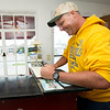 """Traveler Troy Jordan, of St. Joseph, signs the guestbook at Boot's Court Motel on Friday. Jordan, a return visitor, was traveling with a motorcycle group known as the """"Geezers.""""<br /> Globe 