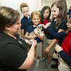 Gabby Goudace, center, holds Marty, a young kitten during Shannon Brower's St. Mary's Elementary third grade class trip to the Joplin Humane Society. Pictured, left is JHS' Tianna Fisher. Children from Brower's class contributed $170 of the $768 raised by the school for the shelter, which received a check from the school on Tuesday during the visit.<br /> Globe | Laurie Sisk