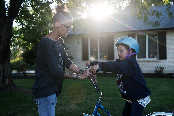 Globe/Roger Nomer<br /> Mandy Gaston helps her partner's daughter Lily Compton, 8, with her bike on Wednesday evening.