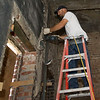Chris Metoyer removes plaster on the first floor of the Hurlbut Building that Contractor Jeff Neal, of Neal Group Construction,  is renovating for office space on at 212 S. Joplin. The building was constructed in 1921 and served as a mortuary before housing the Salvation Army for decades.<br /> Globe | Laurie Sisk