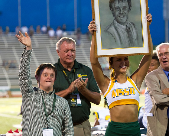 Longtime Missouri Southern basketball assistant Robbie Corn waves to the crowd as he is recognized as one of the latest inductees into the MSSU Hall of Fame on Saturday at Fred G. Hughes Stadium. Also pictured are his father, former MSSU basketball coach Robert Corn and MSSU cheerleader Samantha White.<br /> Globe | Laurie Sisk