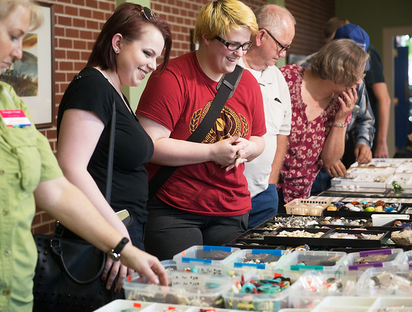 Globe/Roger Nomer<br /> Madison Wilson, left, and Alex Gifford look over items at the Tri-State Gem and Mineral Society Annual Show on Friday at the Joplin Museum Complex. The show continues today and Sunday.