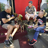 "From the left: Greg Sims, of Fido Friendly magazine, visits with Robert Martin and Jessi Webb, of Golden Paws Pet Resort, during a fundraising stop on Tuesday. Sims is in the midst of a 15-stop nationwide tour from Los Angeles to Chicago to help raise money for no-kill shelters. Also pictured are ""Daisy Mae."" front and ""Johnny Cash."" both former rescue dogs. <br /> Globe 