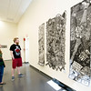 Bronwyn Clay, left and Elias Stubblefield check out  St. Louis artist Tom Huck's woodcut trilogy featuring The Temptation of Brandy Baghead, parts I and II and The Transformation of Brandy Baghead during a reception for the opening of the exhibit on Wednesday at Missouri Southern's Spiva Art Gallery.<br /> Globe | Laurie Sisk