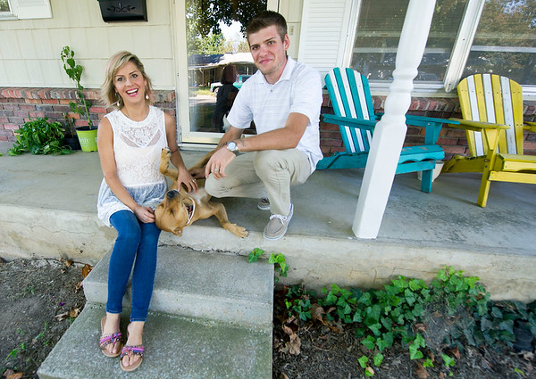 "Jonathan Overman and his fiancee Fina Eaton, sit outside their South Joplin home with their dog, ""Sister""  on Thursday. The couple, who met in drug court, say getting in trouble was the best thing that has happened to them. The couple also are expecting their first child in April.<br /> Globe 