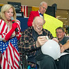 "Ninety four-year-old Alfred ""Bud"" Woods, center pierces a balloon with a piece of coat hanger during the talent portion of the Little Balkans 22nd Annual Senior King and Queen Pageant on Friday at Pittsburg's Meadowbrook Mall. Also pictured from the left: Susie Lundy, Joe Hart and Woods' son, Randy Woods.<br /> Globe 